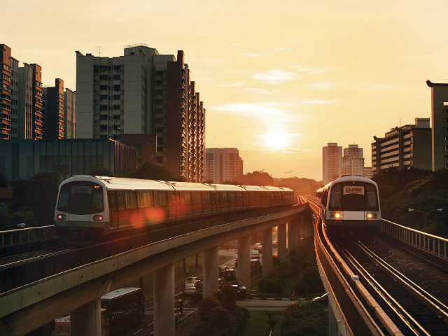 Two MRT trains on the tracks with a sunset behind