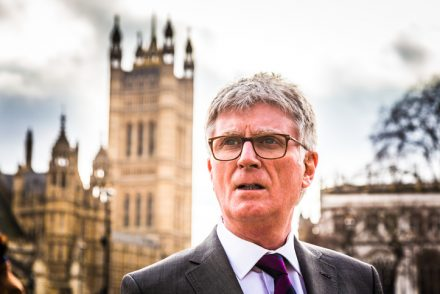 Close up color image depicting a senior businessman, of caucasian ethnicity, standing outside the famous buildings of the Houses of Parliament in Westminster, London, UK. The man is wearing a smart grey suit, white shirt and a purple necktie. He is wearing fashionable spectacles, too. The man has white hair (he is in his 60s) and is looking off past the camera. The famous London architecture is blurred nicely out of focus in the background. Lots of room for copy space.