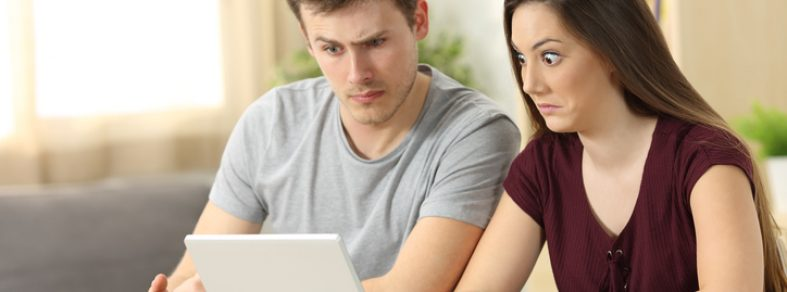 Confused couple studying about renting, sitting in a desk at home