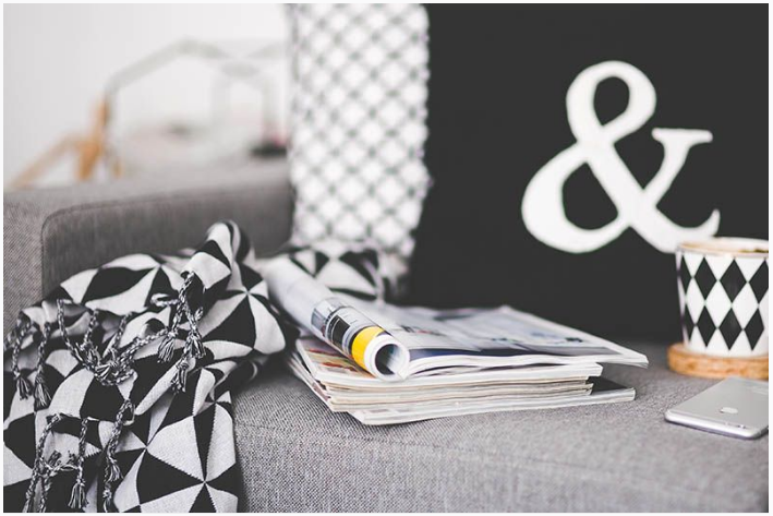 magazines on a sofa, ways to get rid of clutter at home