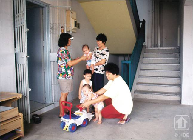 ladies interacting with their neighbours in front of an HDB flat