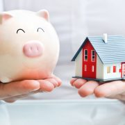 woman holding a piggy bank and a house