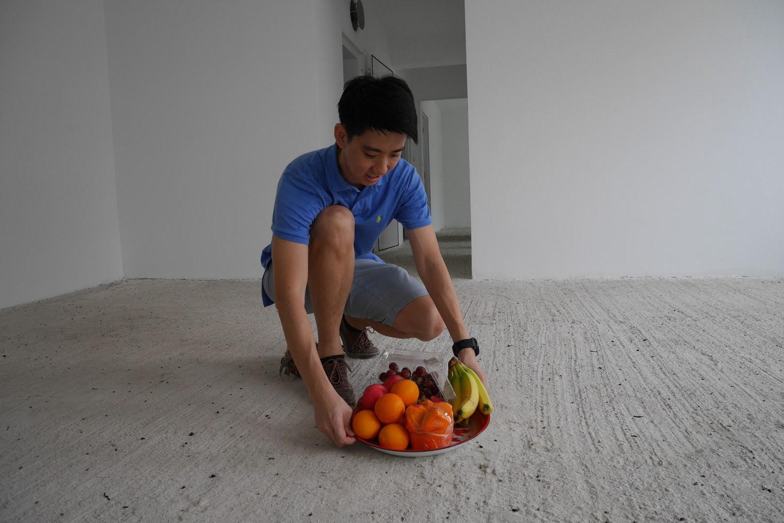 man carrying fresh fruits as part of Chinese ritual for moving in a new house