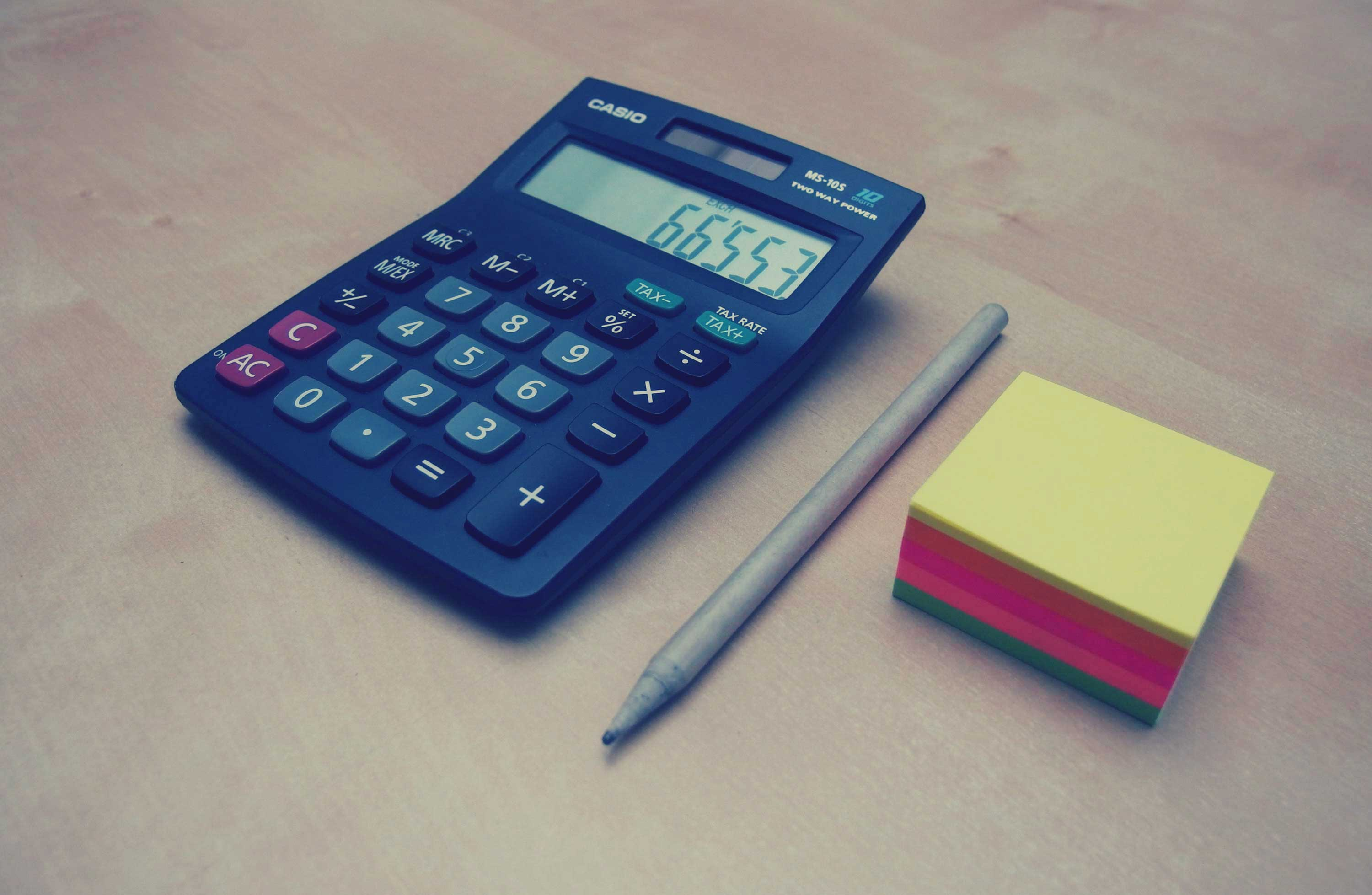 A calculator and stationery to symbolise the importance of calculating the rates of one's mortgage
