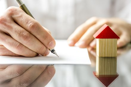 A man signing a document for his home loan, with a small wooden house beside his hand.