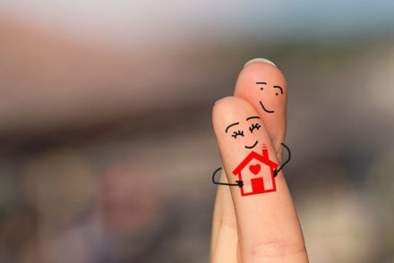 Happy loving fingers holding a house