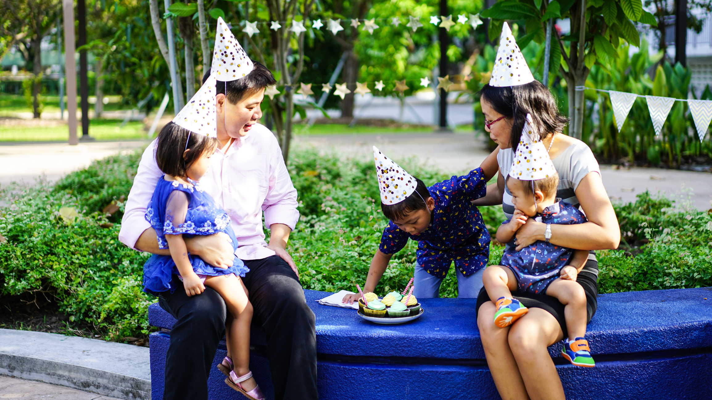 Family in party hats celebrating on public bench