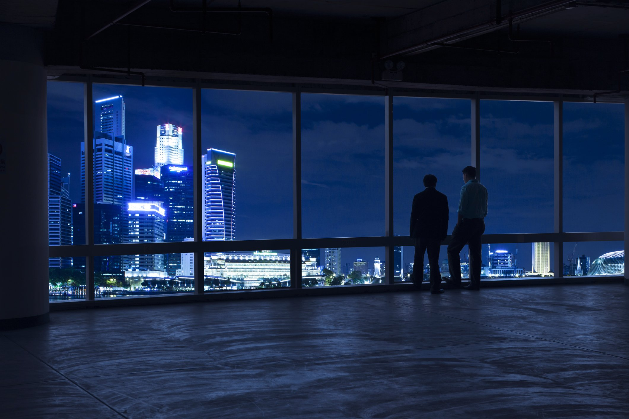 Two businessmen looking out the window at the Singapore city-scape
