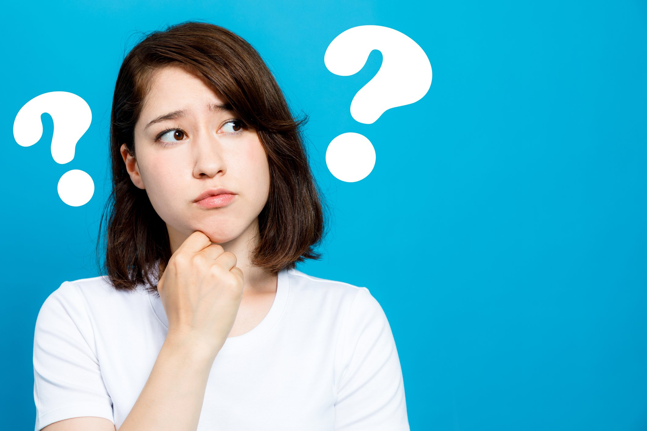Woman between two big question marks