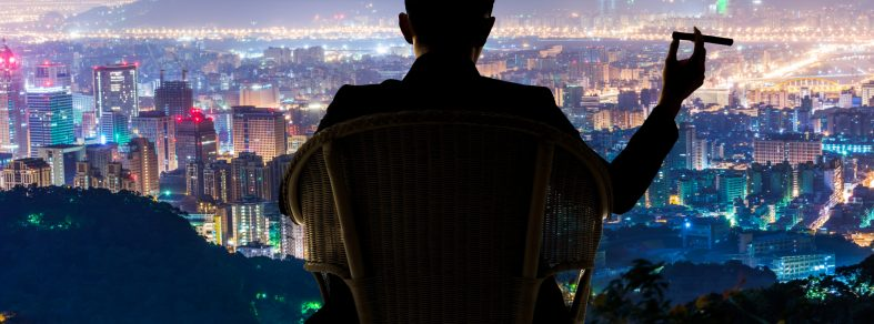 Man in chair with cigar, looking down on 20+ commercial properties