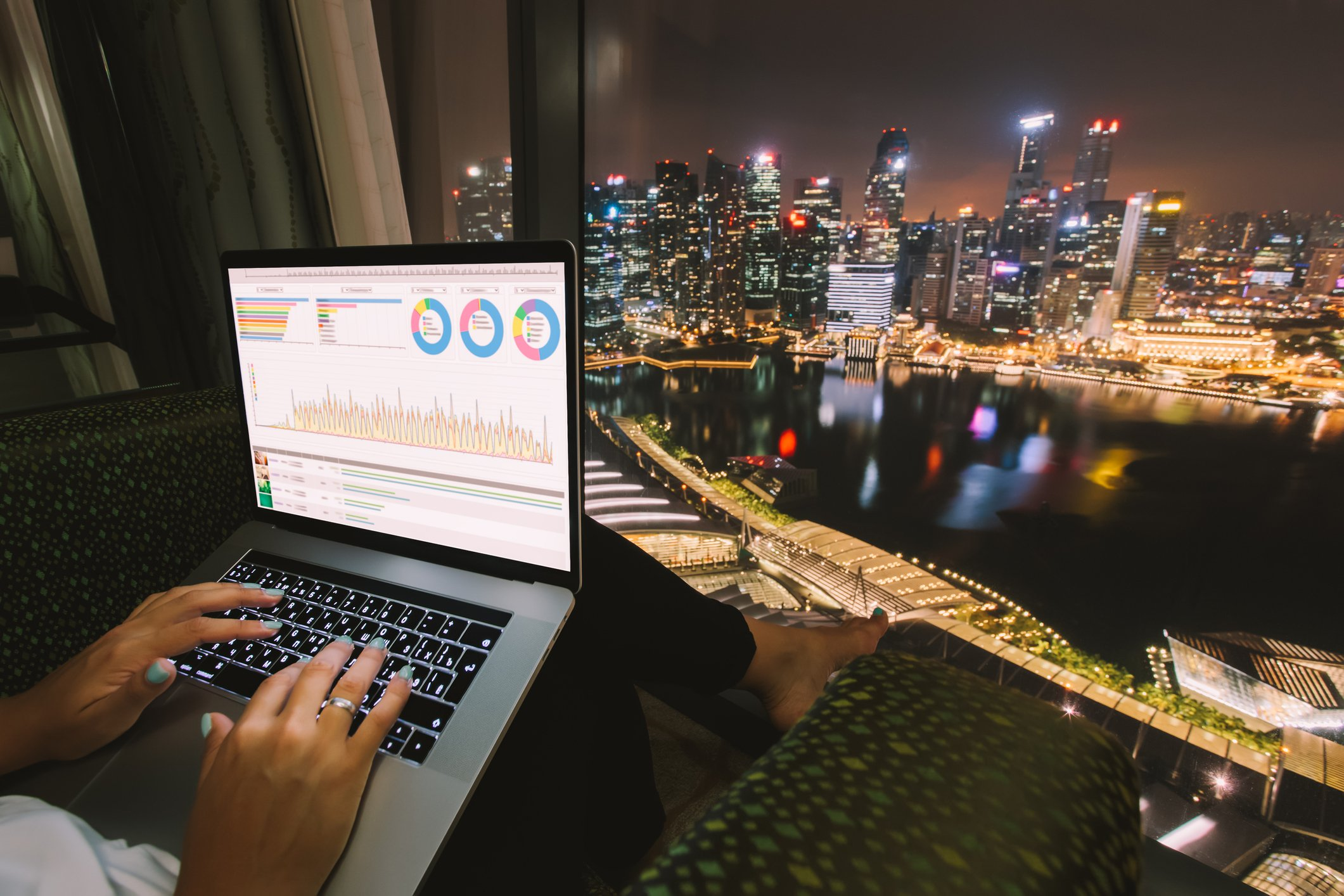Looking out at Singapore city with an open laptop, showing graphs