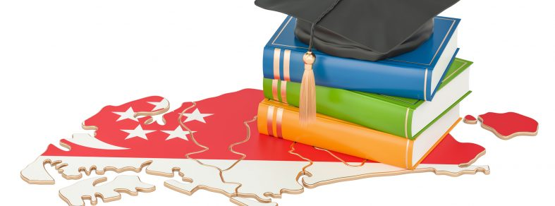 Graduation cap on top of books and a Singapore map