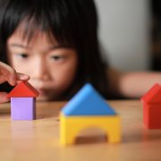 A child building houses with play blocks