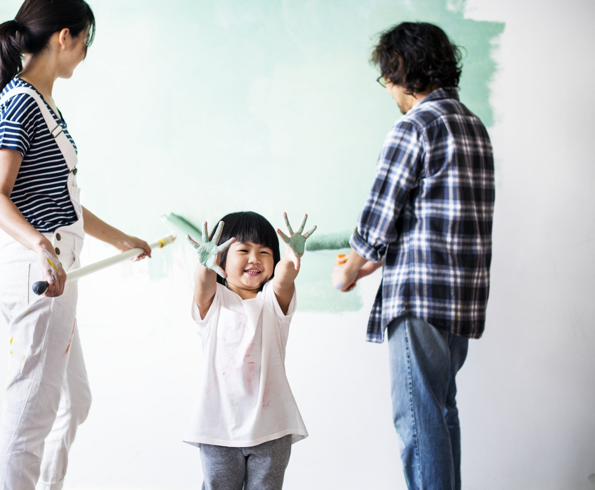 Child holding up hands with green paint, while parents paint the wall