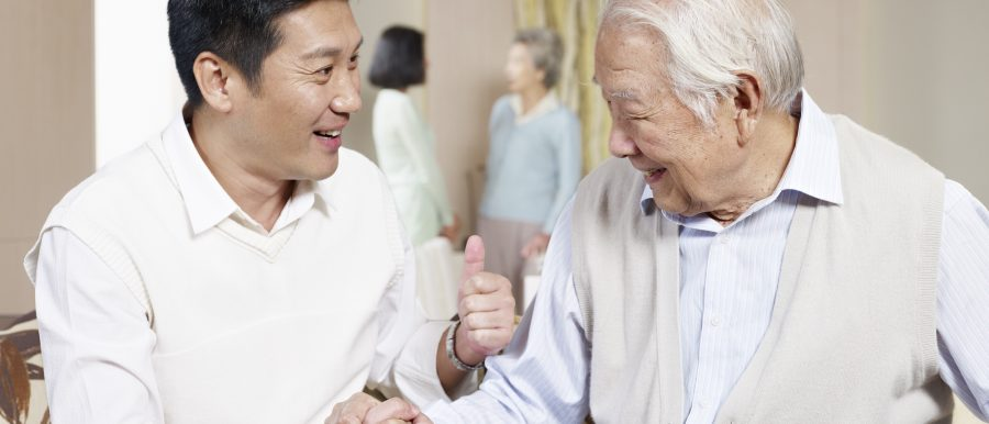 A man shaking his father's hand and making a thumbs-up gesture