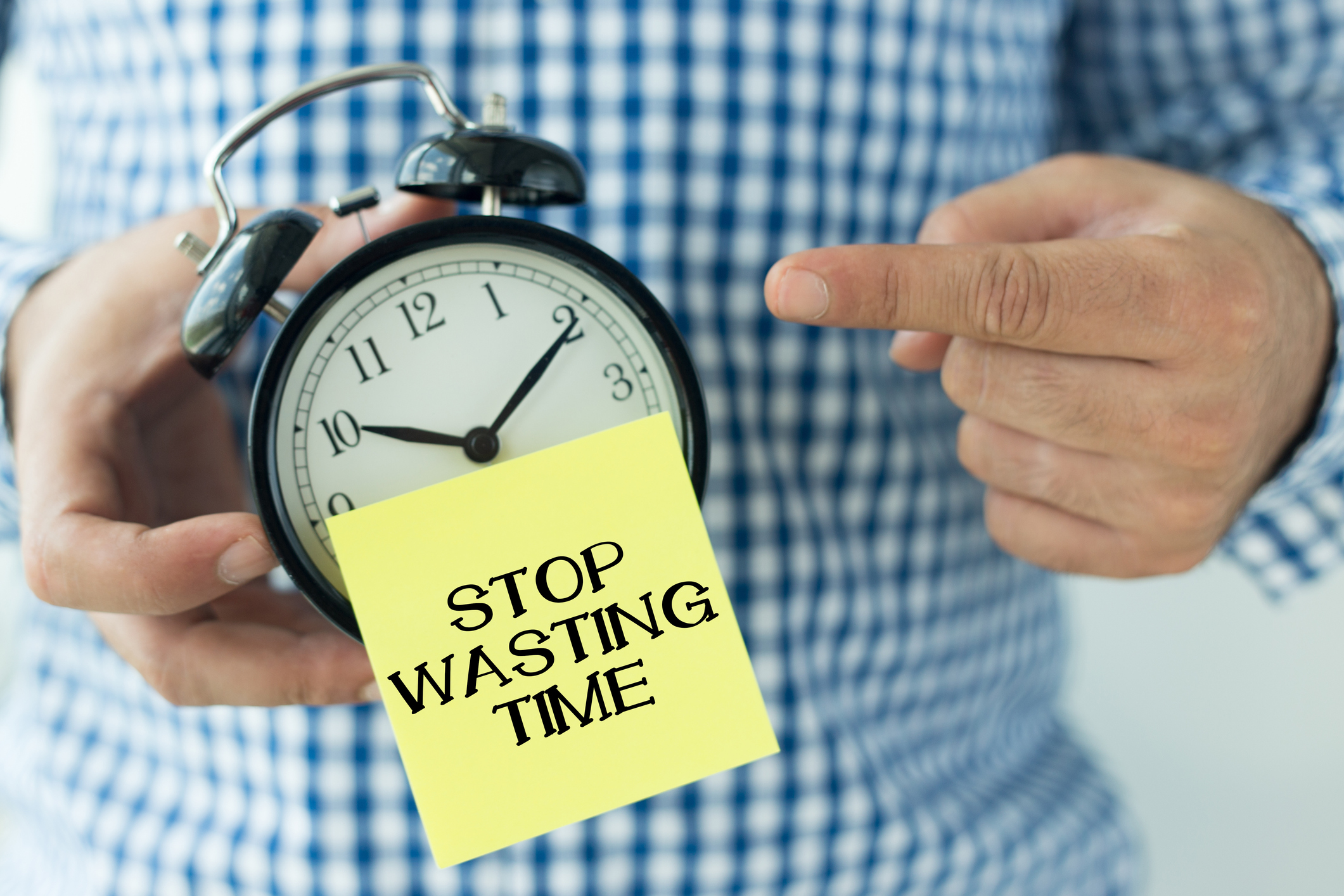 """Alarm Clock with sticky note saying """"stop wasting time"""""""