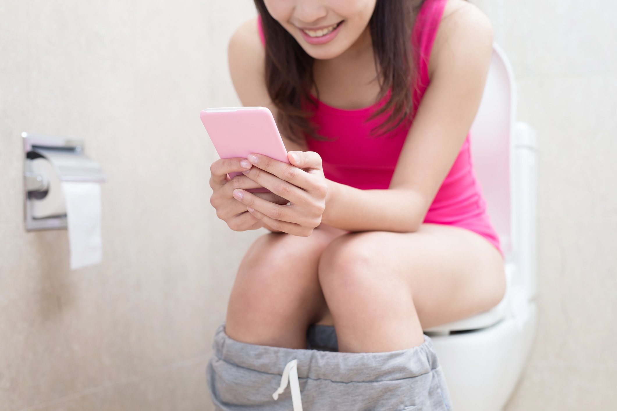 Girl spending excessive time in the bathroom using her phone