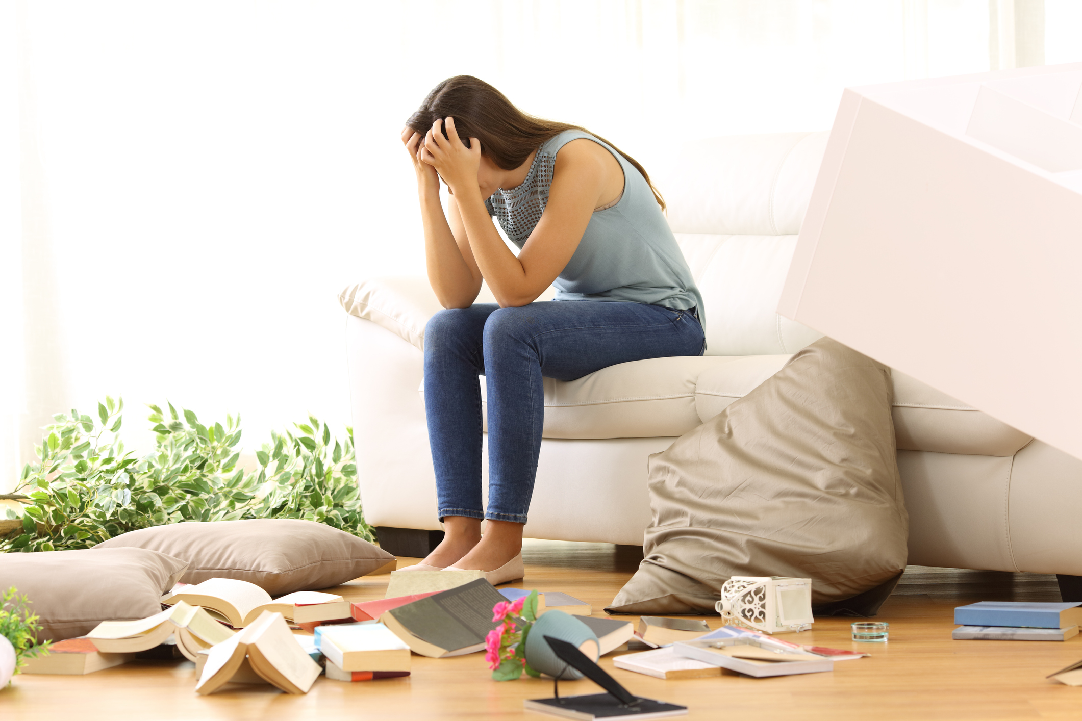 Girl looking distressed at the mess in her apartment