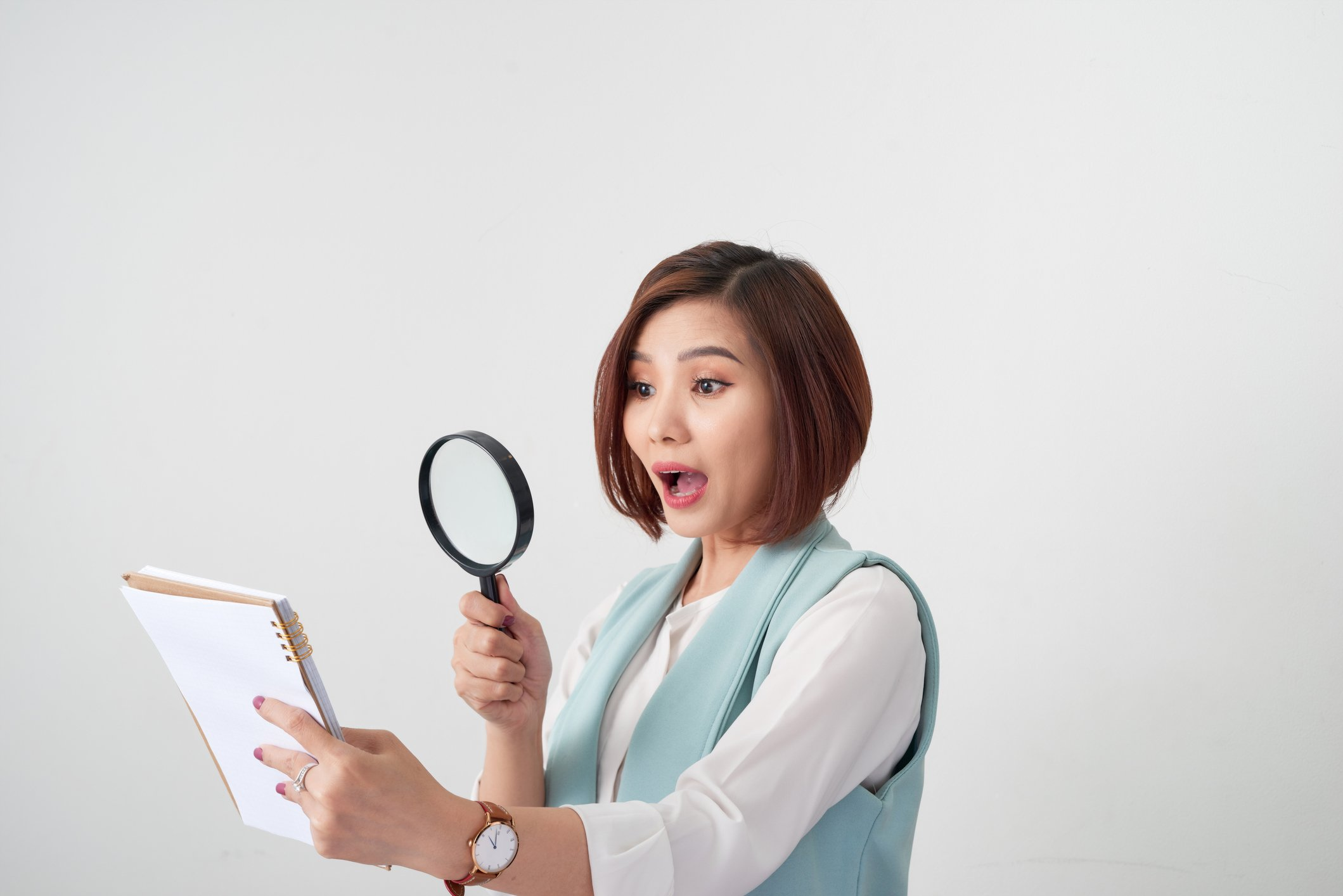 Woman with magnifying glass reading contract