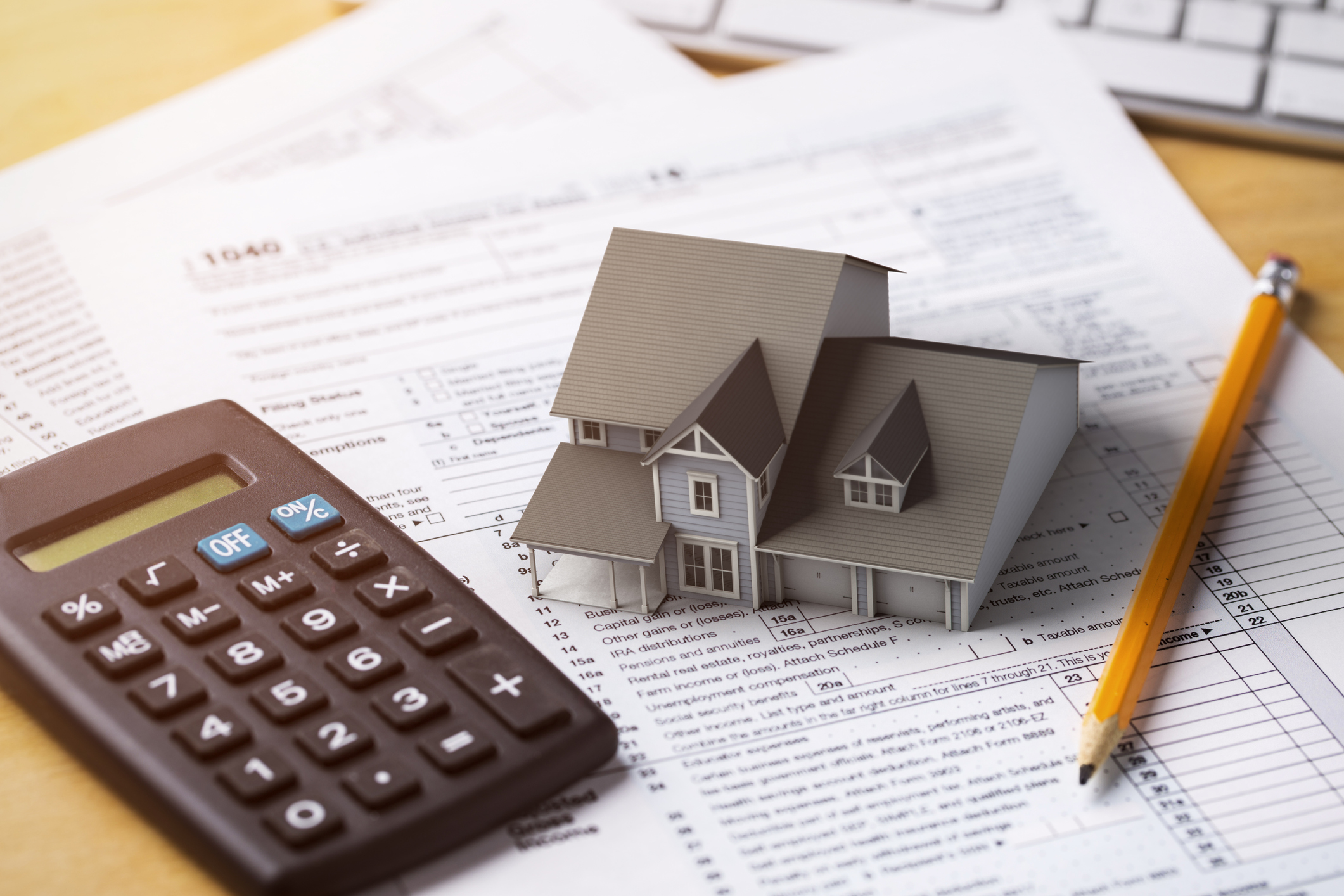 Miniature house on top of loan documents