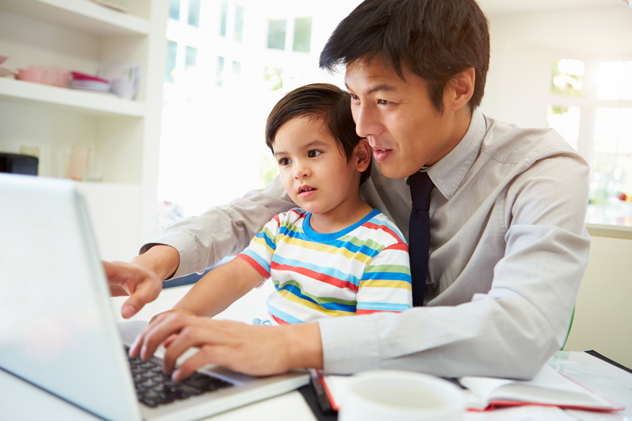 asian dad with kid on laptop