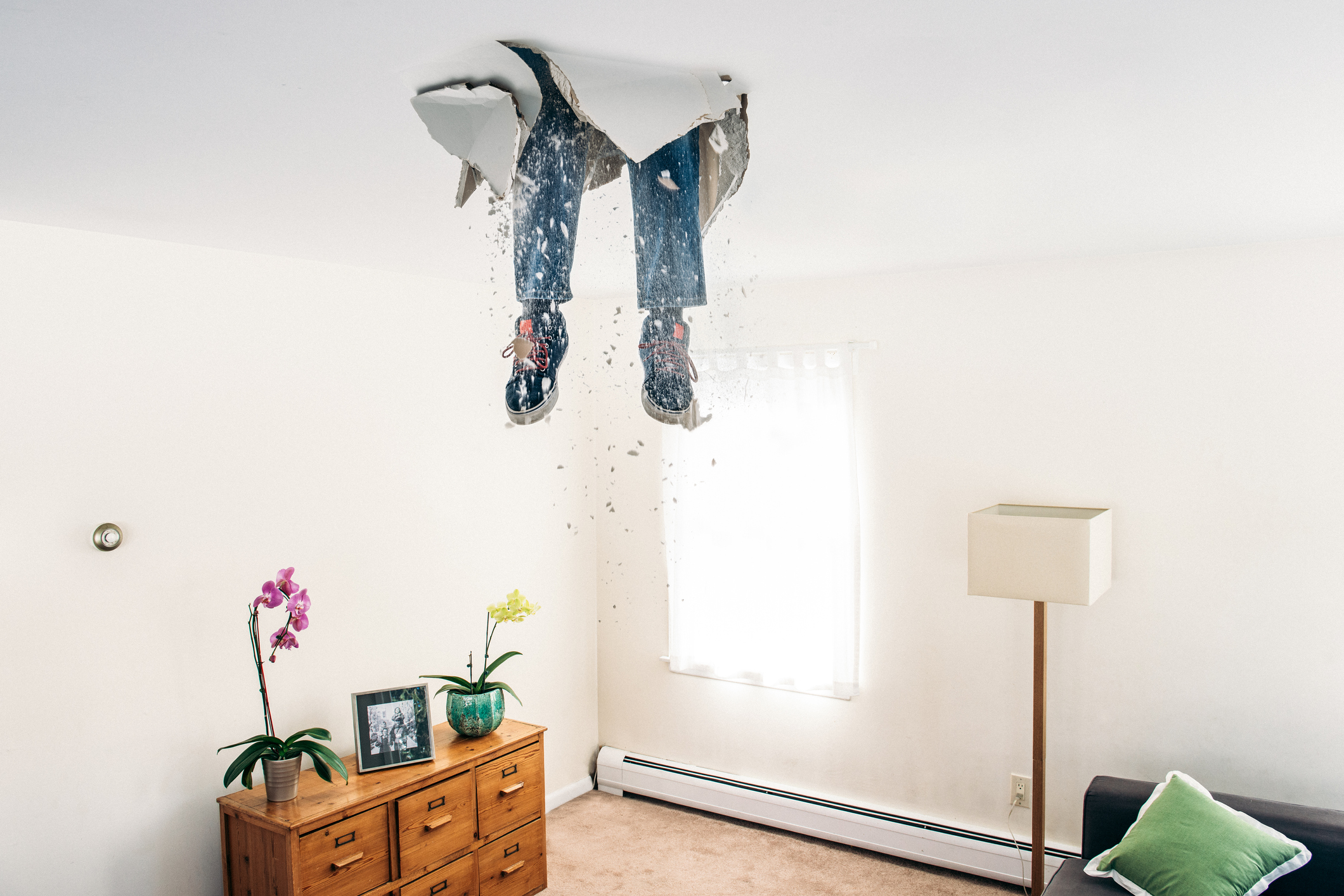 legs sticking out of a false ceiling