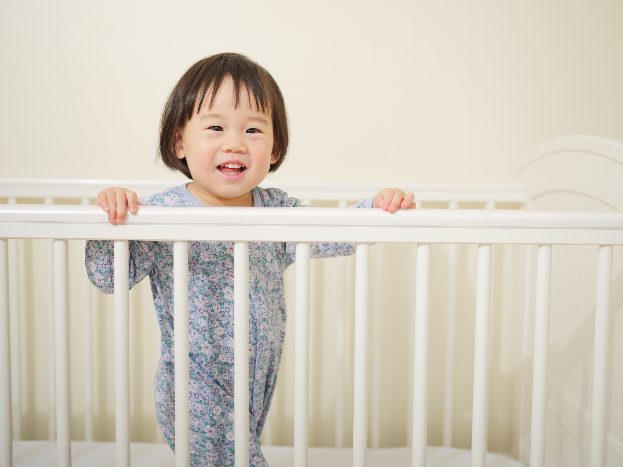 Cute asian baby girl in cot bed