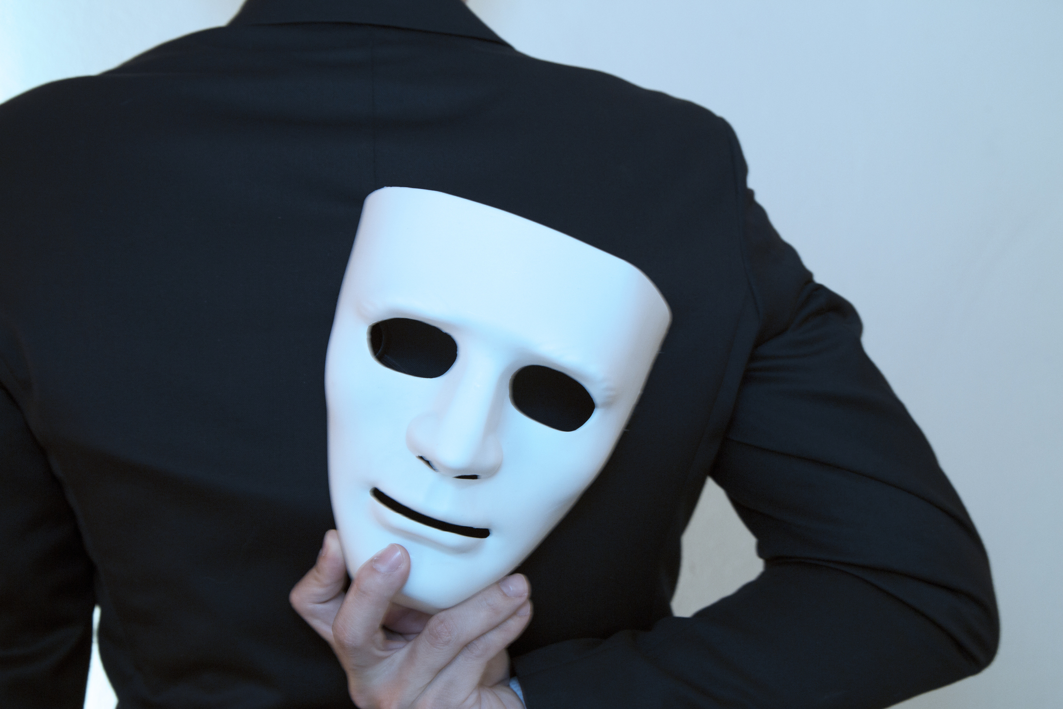 Man holds a mask behind his back