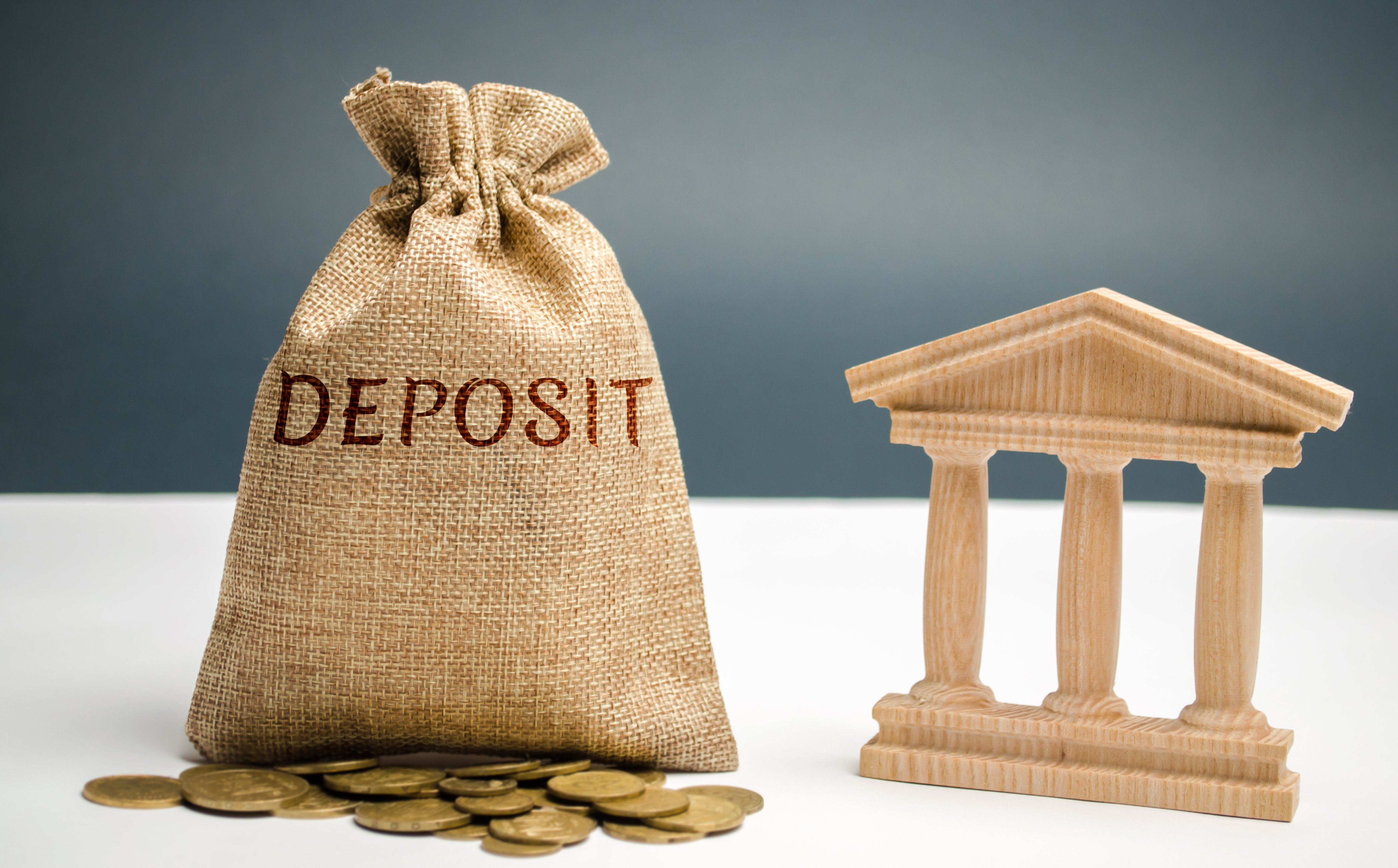 """Moneybag that says """"deposit"""" next to a house"""