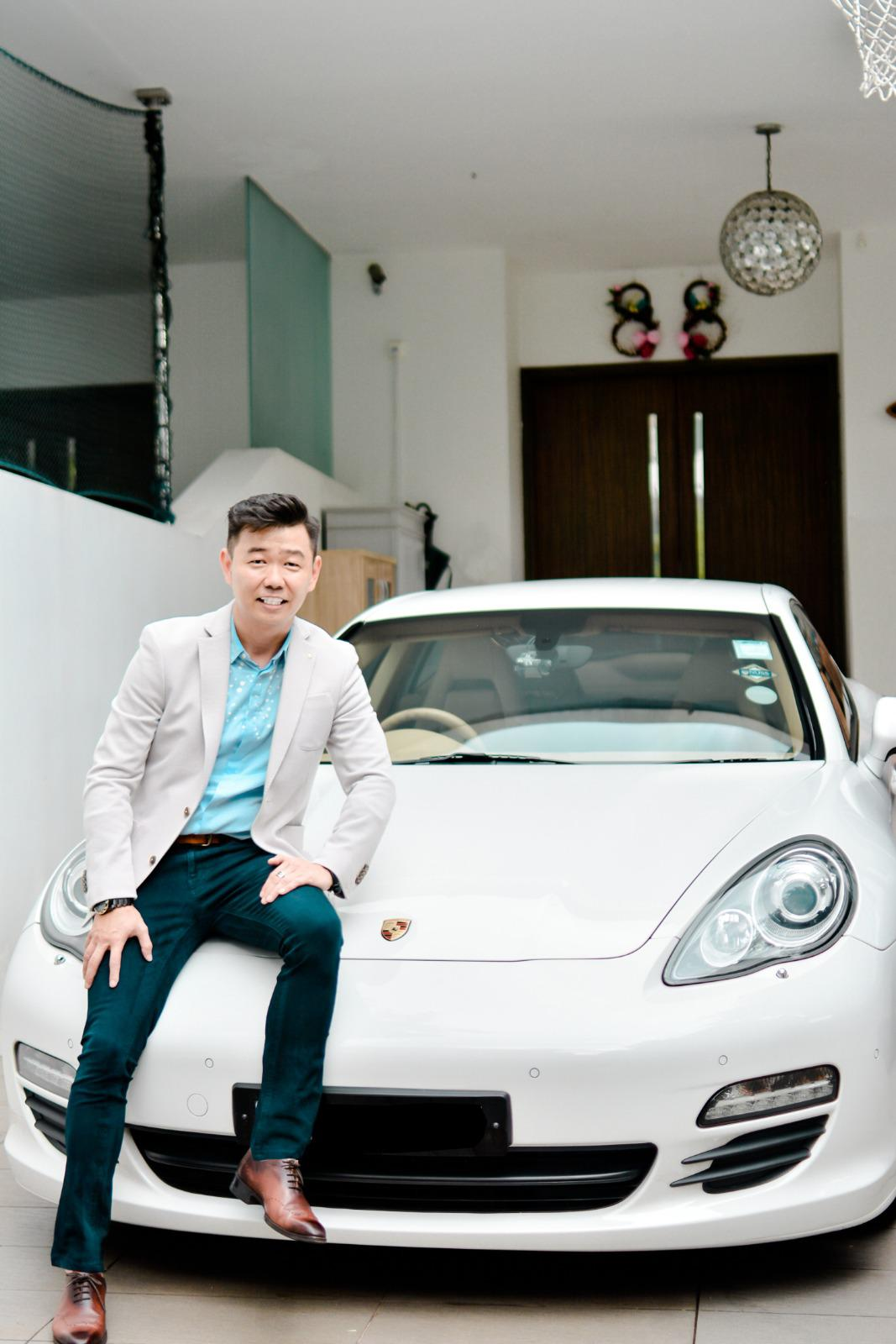 Roy Chong perched on the front of his luxury car