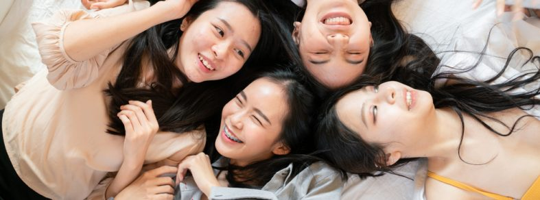 A group of girls lying on a jumbo bed.