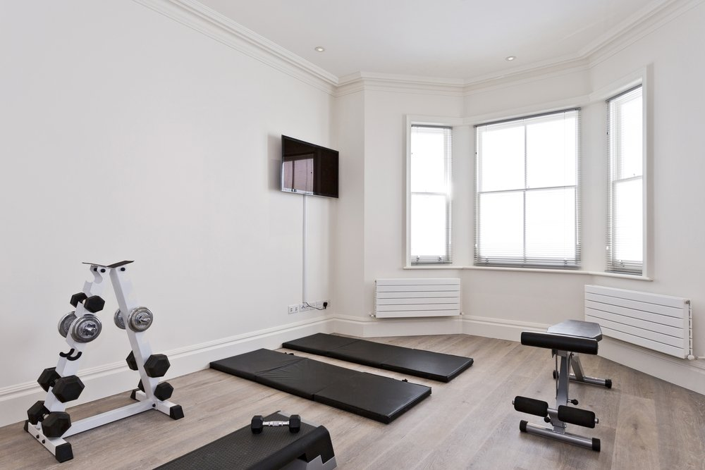 Home gym with equipment such as yoga mat, weights rack and bench