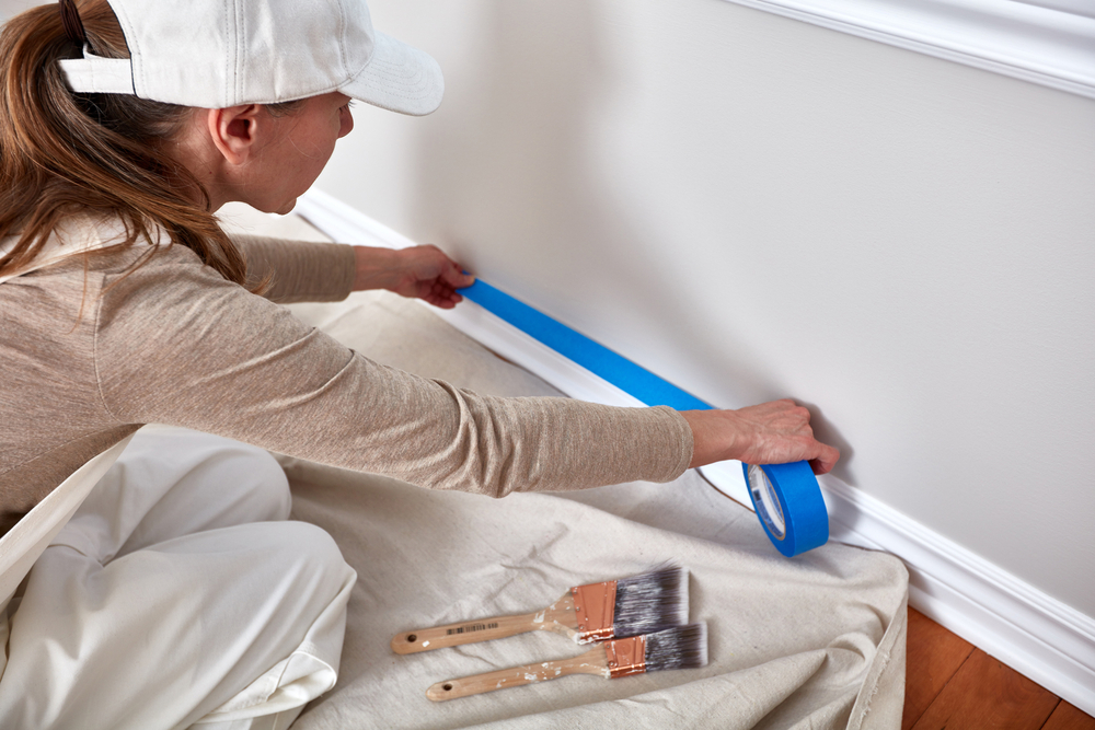 Painter using blue tape to tape off mold and trim before painting