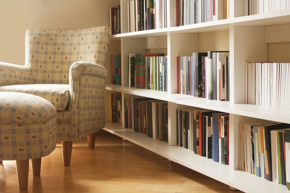 room with books on shelves and armchair