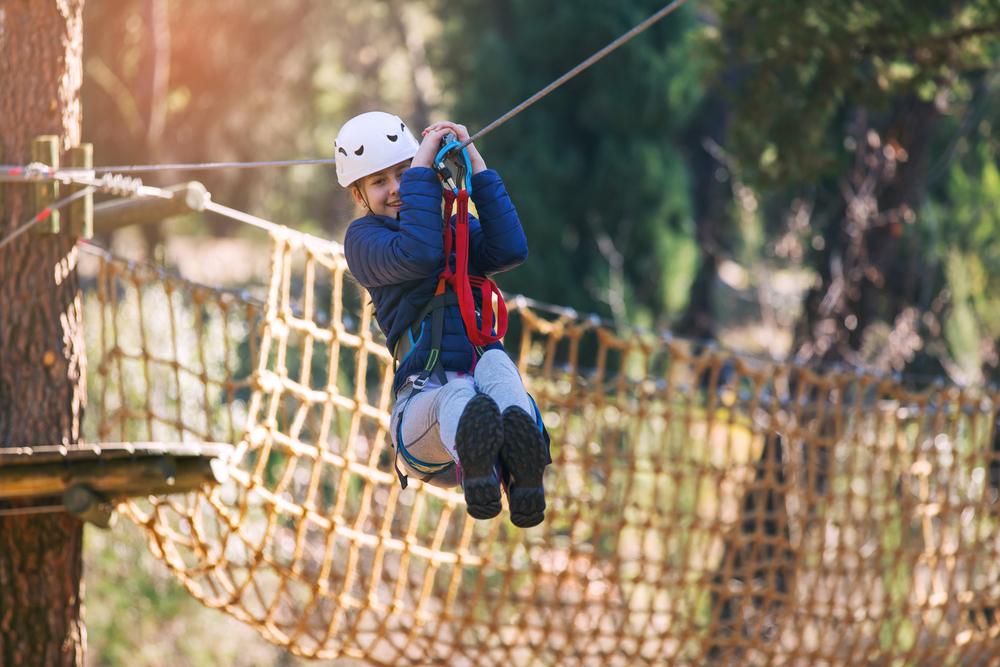 Boy swinging across the zipline at forest adventure, bedok reservoir