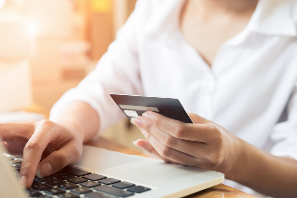 A woman purchasing things online with her credit card.
