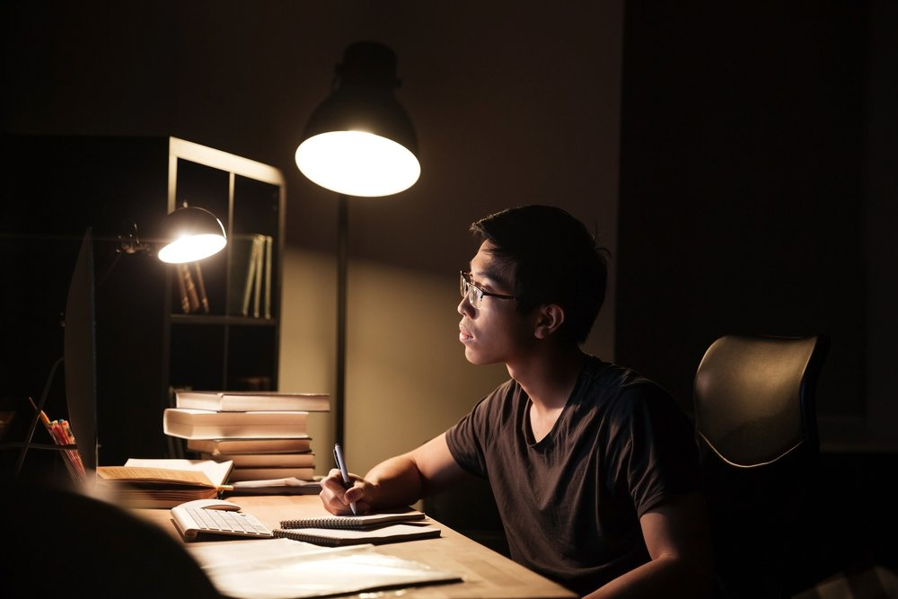 A boy studying with only his desk lamp lighted.