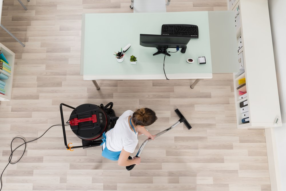 Lady vacuuming her office space