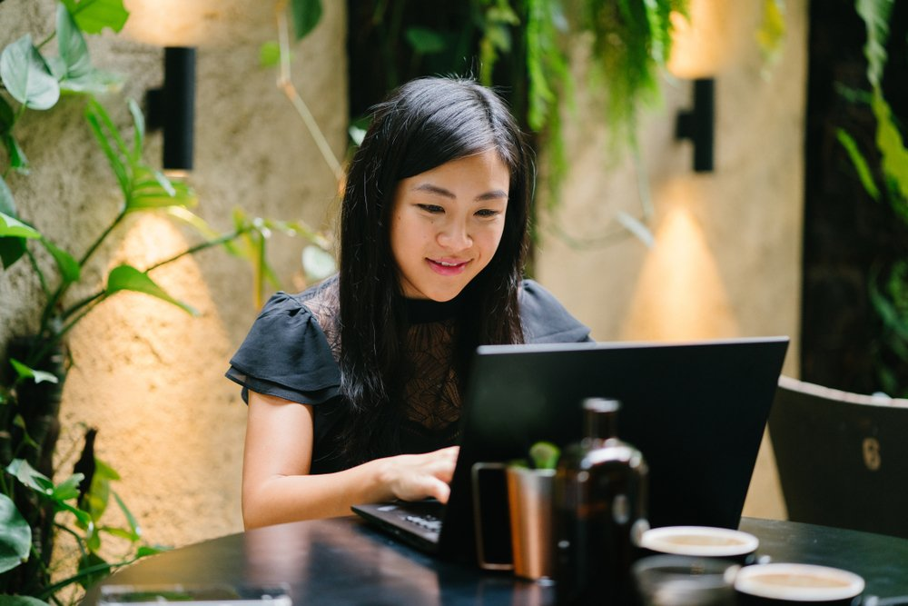 woman working in front of her laptop in an office with plants behind her
