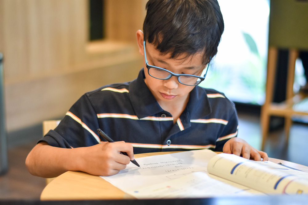 boy wearing glasses studying