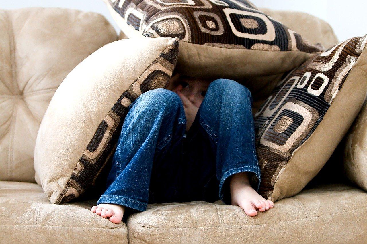 Boy hiding under pillows