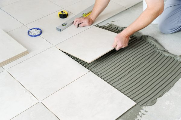 A contractor laying tiles on the cement screed