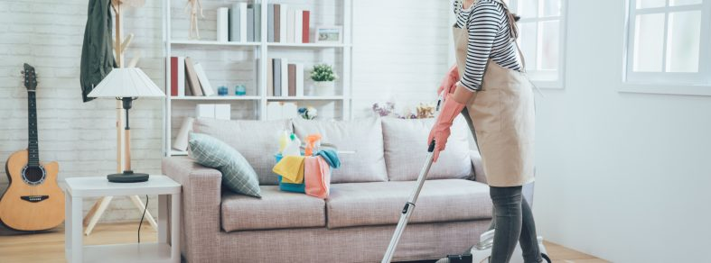 A woman vacuuming living room to allergy-proof home