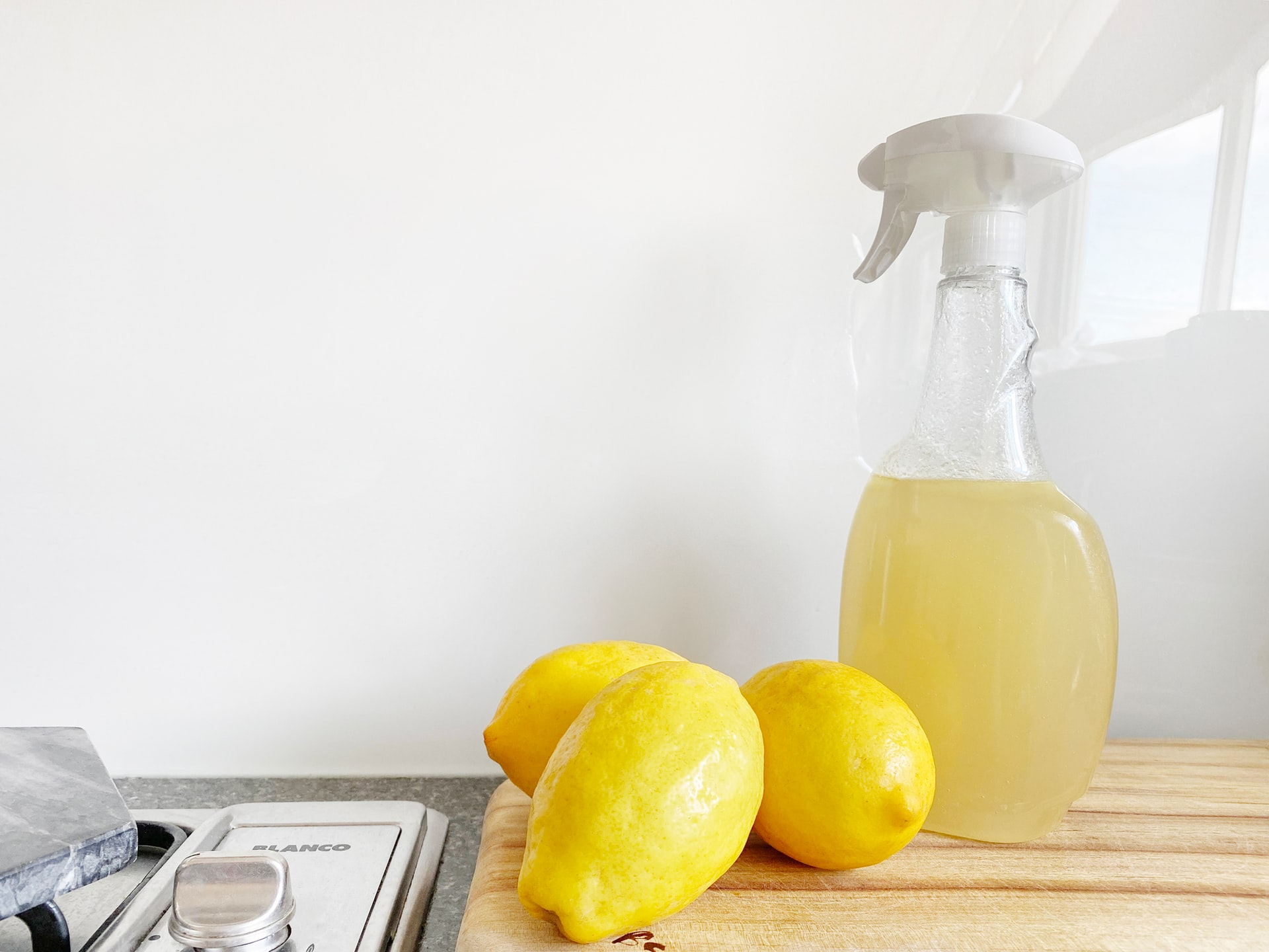 Three lemons and a spay bottle containing a mixture of vinegar and lemon, which can help get rid of ants and termites