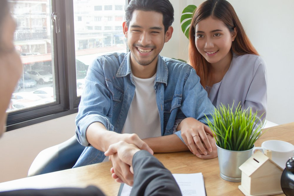 Couple shaking hands with landlord after signing tenancy agreement