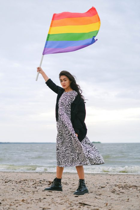 asian woman holding pride flag on beach