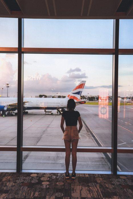 woman at airport lounge looking at airplanes