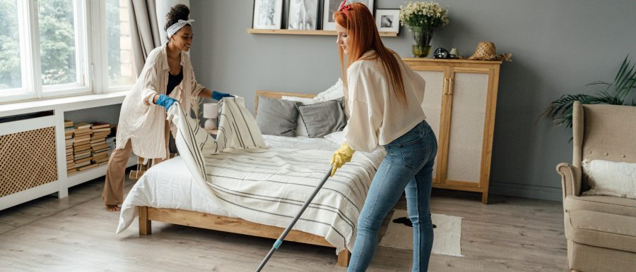 Middle age LGBTQ gay female caucasian couple cleaning bedroom