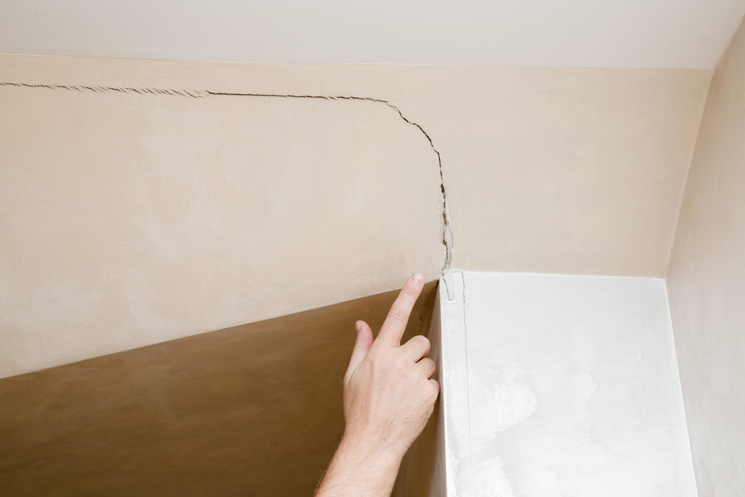 Person pointing out a crack on the wall